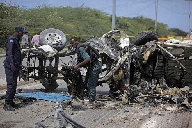 Somali soldiers removing remains of a charred car from the street after the attack.